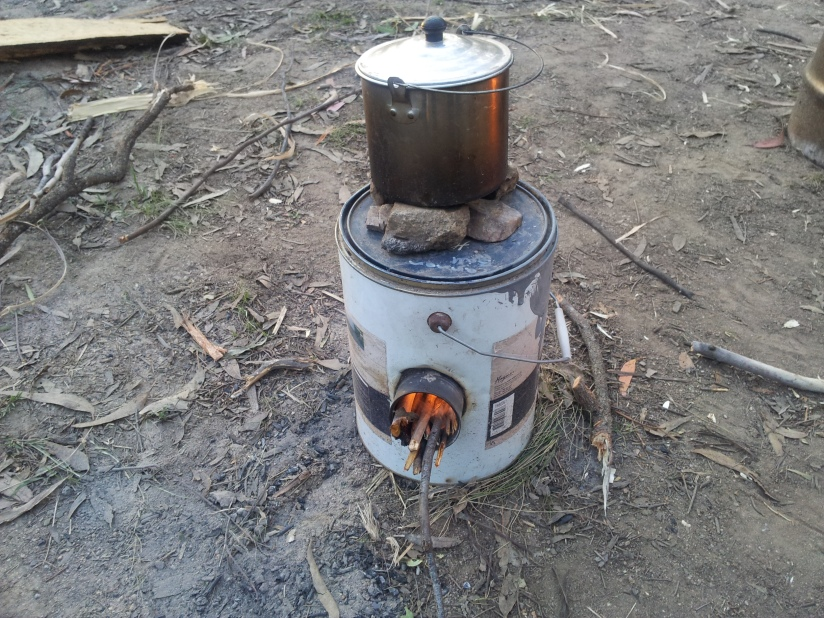 Rocket stove made from a paint can and 3 smaller 300 gram food cans. Small rocks used to create gap between pot and stove